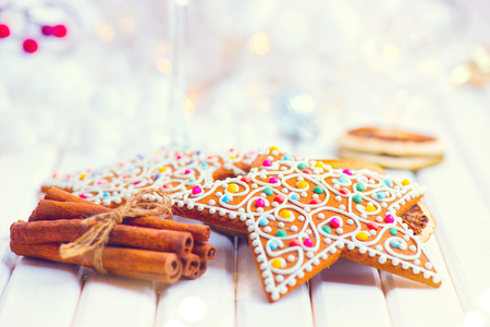 Christmas gingerbread cookies and cinnamon sticks on white wooden table decorated with garland and candles Banque d'images