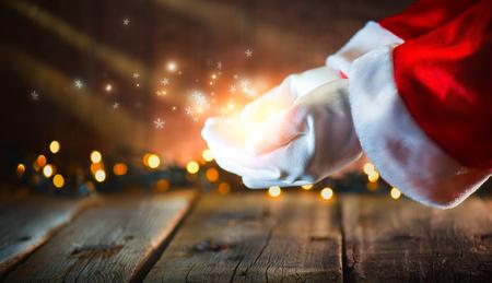 Scène de Noël. Père Noël montrant des étoiles brillantes et de la poussière magique dans les mains ouvertes. Produit proposé