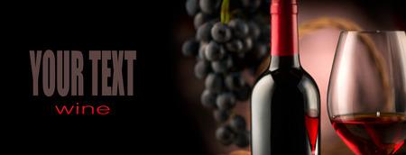 ワイン。ボトルと黒背景に熟した葡萄と赤ワインのガラス 写真素材