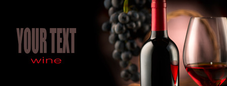 Du vin. Bouteille et verre de vin rouge avec des raisins mûrs sur fond noir