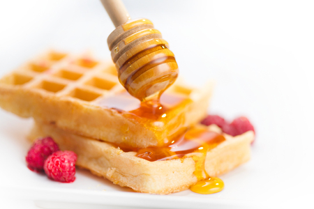 Belgian waffles with honey and berries closeup over white background Stock Photo