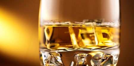 Whisky on the rocks. Glass of whiskey with ice over amber background