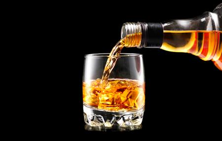 黒の背景上に瓶から注いでウイスキー。ウィスキーのオンザロック