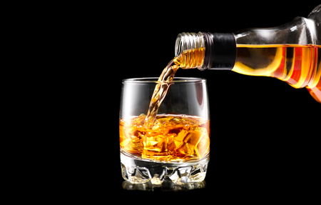 Whisky pouring from the bottle over black background. Whiskey on the rocks Reklamní fotografie