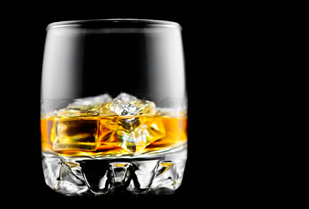 Whisky on the rocks. Glass of whiskey with ice isolated on black background Stock Photo