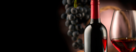 Wine. Bottle and glass of red wine with ripe grapes over black background 免版税图像