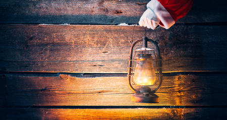 Christmas scene. Santa Claus hand holding vintage oil lamp over holiday wooden background Stock Photo