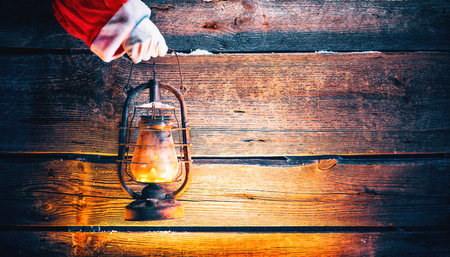 Christmas scene. Santa Claus hand holding vintage oil lamp over holiday wooden background Banque d'images