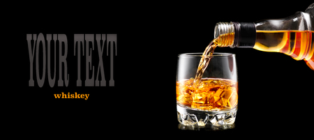 Whisky pouring from the bottle over black background. Whiskey on the rocks 스톡 콘텐츠