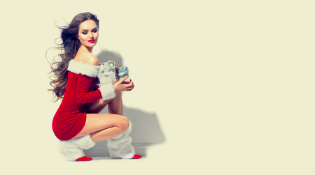 Sexy santa. Christmas beauty girl wearing red dress holding gifts. Brunette young woman portrait Stock Photo