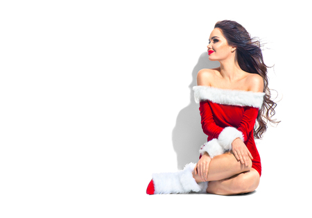 Christmas beauty model girl. Sexy brunette young woman wearing red santa dress