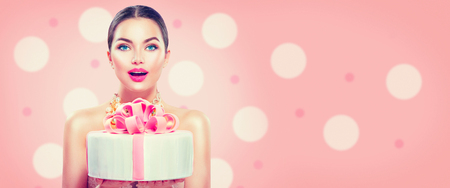 Fashion model girl holding beautiful party or birthday cake isolated on pink background. Wide angle