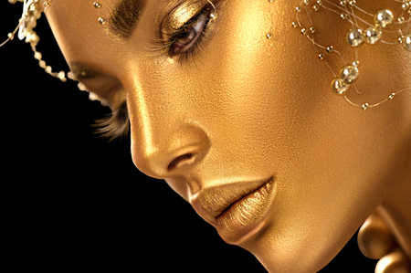 Beauty model girl with holiday golden shiny professional makeup closeup portrait. Gold jewelry and accessories