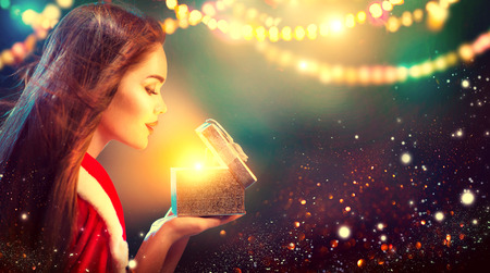 Christmas scene. Beauty brunette young woman in party costume opening gift box over holiday blurred background