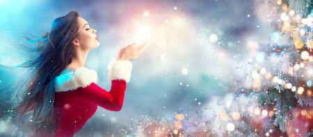 Escena navideña. Sexy santa Joven morena en traje de fiesta soplando nieve sobre fondo borroso de vacaciones