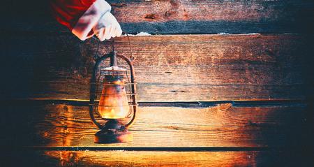 Christmas scene. Santa Claus hand holding vintage oil lamp over holiday wooden background Standard-Bild