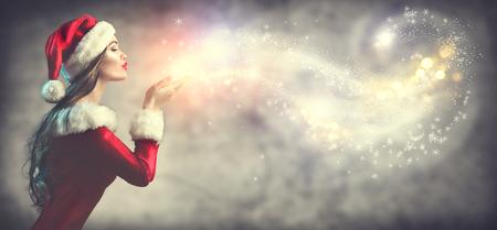 크리스마스 장면. 섹시한 산타. 휴일 흐리게 배경 위에 눈을 불고 파티 의상에서 갈색 머리 젊은 여자