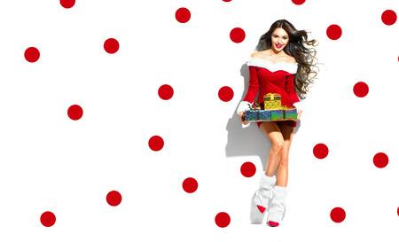 Scène de Noël. Sexy Santa. Fille de modèle de beauté portant le costume de fête rouge tenant des cadeaux