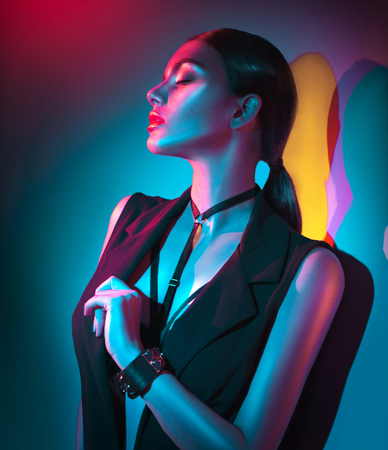 Portrait of sexy young woman in black clothes, fashion accessories, bright makeup in neon light 스톡 콘텐츠