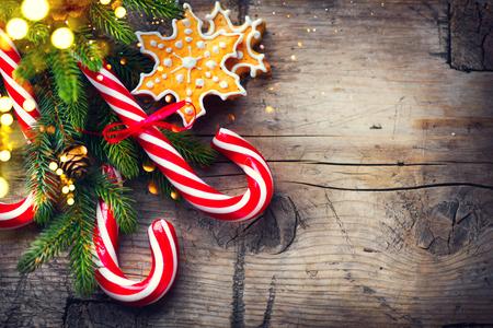 Fond de vacances de Noël avec des biscuits de pain d'épice, la canne de bonbon et la frontière à feuilles persistantes sur la table en bois