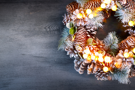 Christmas vintage background. Holiday evergreen tree wreath decorated on dark wooden table