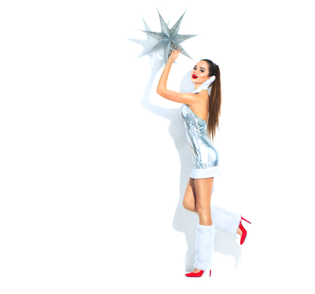 Christmas scene. Beauty model girl in silver party costume holding Christmas star over white background Stock Photo