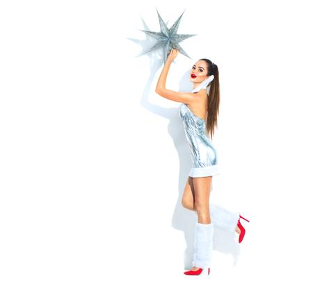 Scène de Noël. Fille de modèle de beauté en costume de fête argent tenant l'étoile de Noël sur fond blanc
