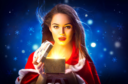 Christmas scene. Beauty brunette young woman in party costume opening gift box over holiday night background