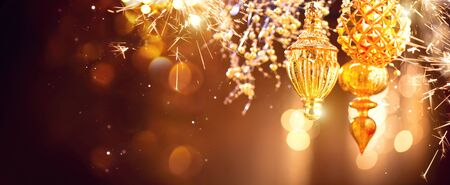Christmas and New Year golden decorations. Abstract blinking holiday background. Wide angle Stock Photo