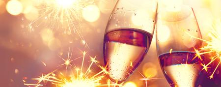 Célébration de Noël. Flûtes avec champagne mousseux sur fond lumineux de vacances
