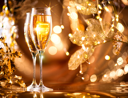 Christmas celebration. Flutes with sparkling champagne over holiday glowing background