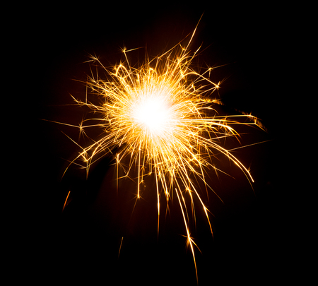 Bright sparks on deep black background closeup. Party holiday sparkler isolated on black