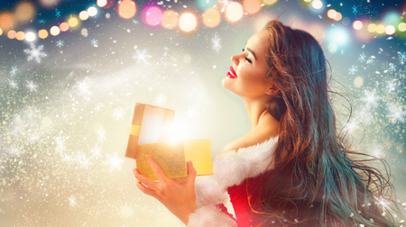 Christmas scene. Beauty brunette young woman in party costume opening gift box over holiday background