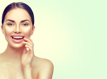 Beauté femme brune spa toucher son visage et souriant. Blanchissement dentaire