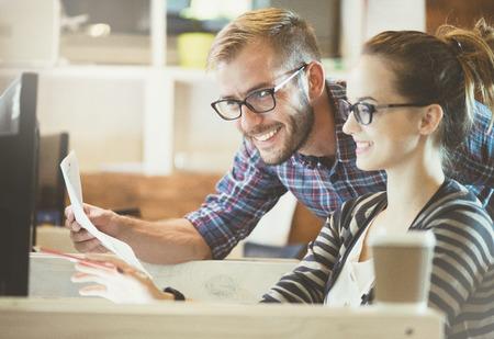 Couple de vêtements de travail à l'aide d'ordinateur dans le bureau. Deux collègues travaillant ensemble sur un design de produit innovant dans un studio de création Banque d'images