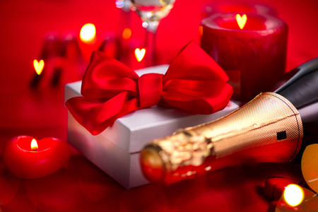 Valentines Day romantic dinner. Date. Champagne, candles and gift box over holiday red background