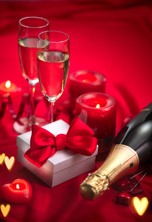 Valentine's Day romantic dinner. Date. Champagne, candles and gift box over holiday red background
