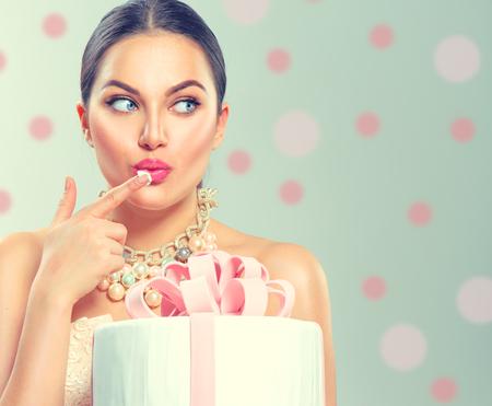 Divertida chica modelo de belleza alegre celebración gran fiesta hermosa o pastel de cumpleaños sobre fondo verde y degustándolo Foto de archivo - 92992334