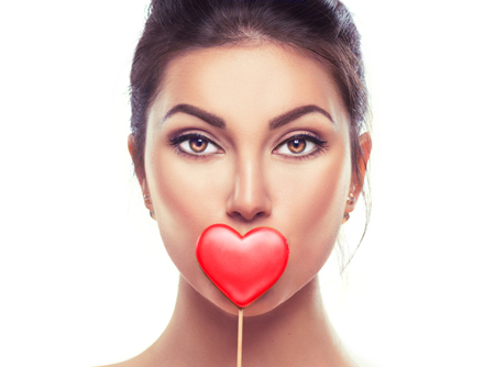 Valentines Day. Beauty surprised young fashion model girl with Valentine heart shaped cookie Banque d'images
