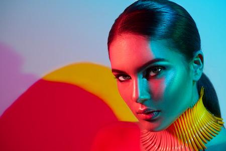 Femme modèle modèle en lumière lumineuse colorée posant. Portrait de belle fille sexy avec un maquillage à la mode
