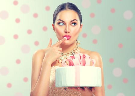 Vorbildliches Mädchen der lustigen frohen Schönheit, das großen schönen Partei- oder Geburtstagskuchen über grünem Hintergrund hält und es schmeckt Standard-Bild