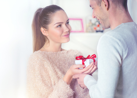St. Valentine's Day. Love concept. Young man giving a gift to his girlfriend