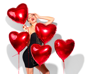 Valentine's Day. Beauty girl with colorful air balloons having fun, isolated on white background