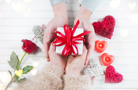 Valentines Day. Young couple hands holding gift box over white wooden background. Love concept. Top view