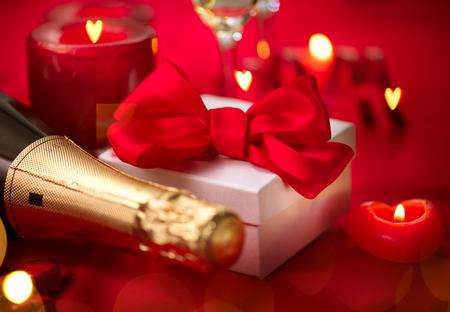 발렌타인 데이 낭만적 인 저녁 식사. 날짜. 휴일 빨간색 배경 위에 샴페인, 양 초 및 선물 상자