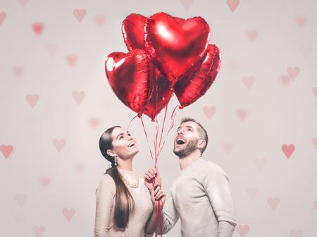 La Saint Valentin. Heureux couple joyeux. Portrait de souriant beauté fille et son beau petit ami tenant des tas de ballons à air en forme de coeur