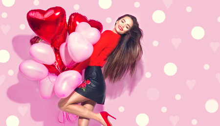 Valentines Day. Beauty girl with colorful air balloons having fun over pink background