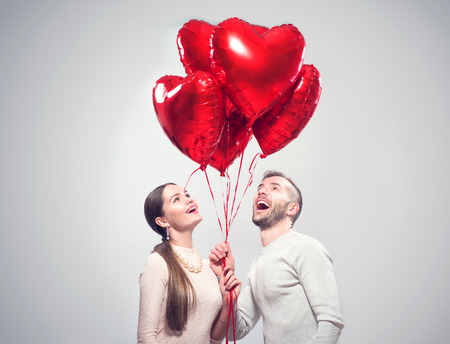 Valentines Day. Happy joyful couple. Portrait of smiling beauty girl and her handsome boyfriend holding bunch of heart shaped air balloons