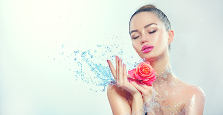 Spa woman. Beauty smiling girl with splashes of water and rose in her hands. Skincare concept