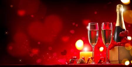 Dîner romantique pour la Saint-Valentin. Champagne, bougies et coffret cadeau sur fond rouge de vacances Banque d'images